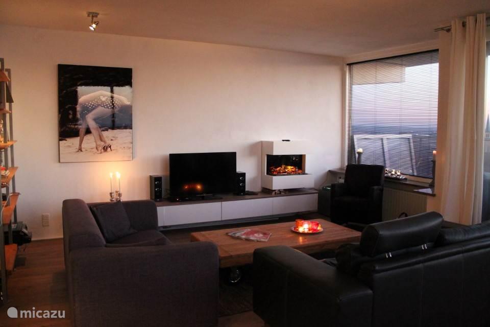 Gezellige moderne woonkamer met sfeerhaard en smart tv