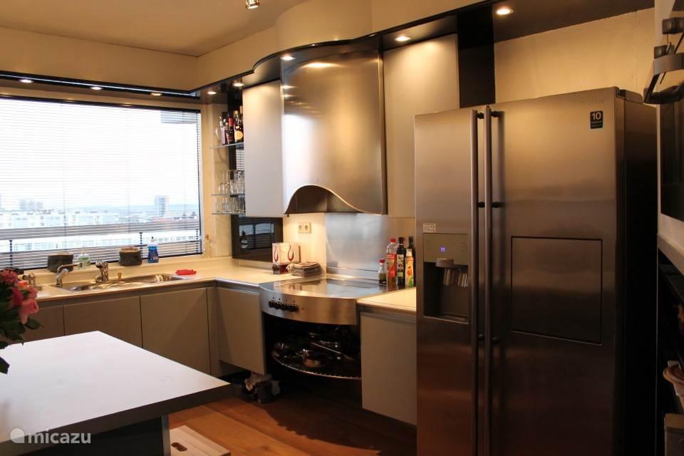 Keuken met keramische kookplaten /  oven / combi magnetron, vaatwasser en amerikaanse koelkast.