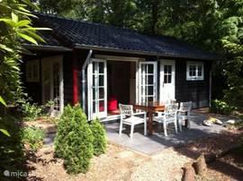 Onze gezellige vakantiewoning met in de zomer een eettafel, stoelen en parasol op het terras om heerlijk te eten :-)