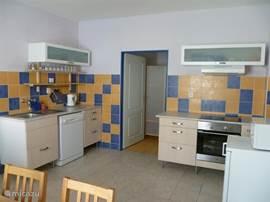 Keuken met vaatwasser, keramische kookplaat, elektrische oven, koelkast, waterkoker en magenetron