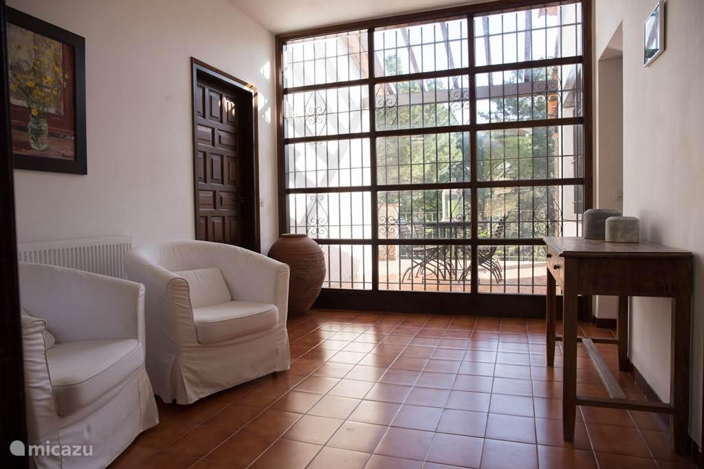 Hal met glazen pui en gietijzeren smeedwerk en patio van 4x5 m2 op balkon terras