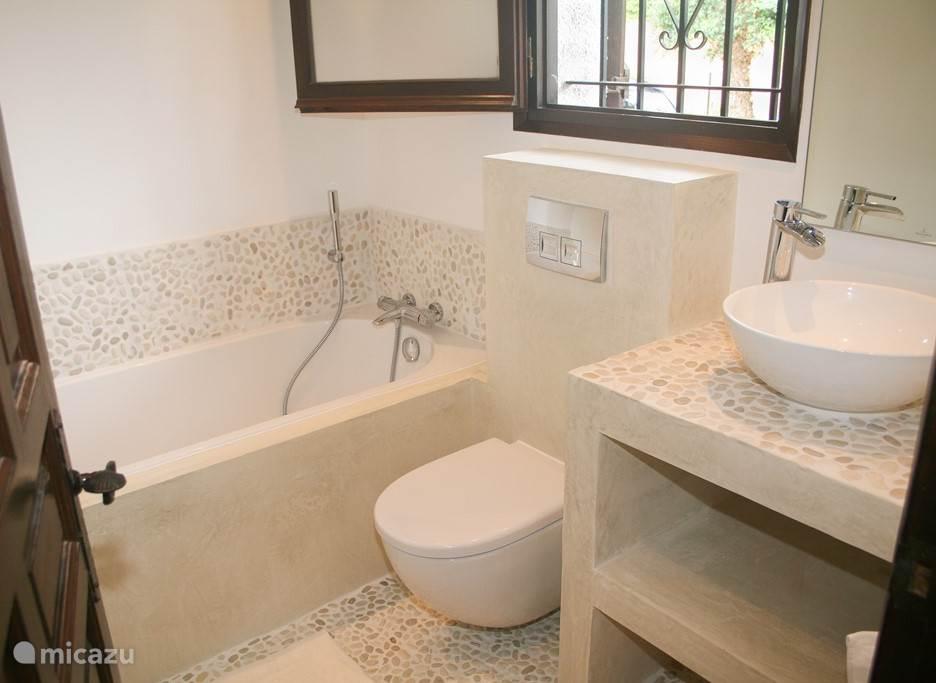 Badkamer met wasbak, ligbad en toilet