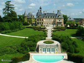 Een luchtfoto van het kasteel met het kasteelzwembad.