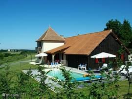 Het (verwarmde) zwembad ligt naast het huis. Op het grote vlonder staan diverse ligbedden.