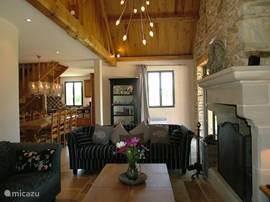 Door het verhoogde plafond komt de grote Franse schouw goed tot zijn recht. De woonkamer is ruim en ingericht met 2 grote comfortabele banken.