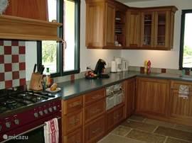 De open keuken heeft een groot gasfornuis met 5 pitten en een extra brede oven. Naast een afwasmachine is er een magnetron en een Amerikaanse koelkast met ijsblokjesmachine. Hierin kunt u makkelijk al uw boodschappen kwijt.
