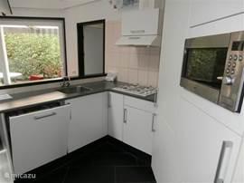 De zeer praktisch ingerichte keuken met afwasmachine
