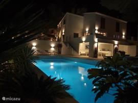 Aanzicht vanaf zijde zwembad tijdens avond