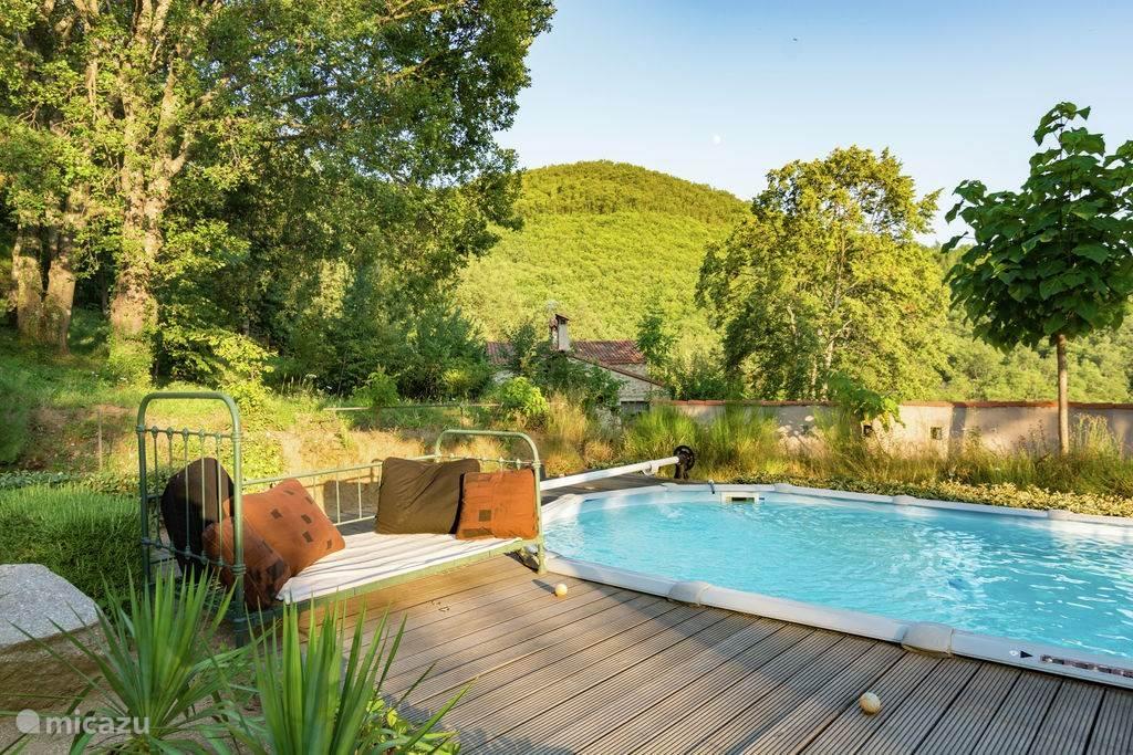 Het zuiver met bronwater gevulde zwembad met terras en op de achtergrond de oude gerenoveerde Catalaanse Mas.