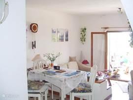 Doorkijk vanuit de keuken. U ziet de eettafel, de salon en de openslaande deuren naar het terras