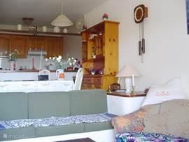 Zicht vanuit de salon met vaste zitbanken, richting keuken.