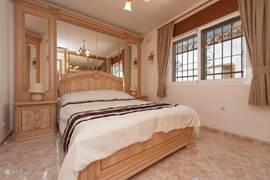 Een van de drie slaapkamers. Ze zijn allemaal voorzien van tweepersoons bedden en ruime kastruimte.