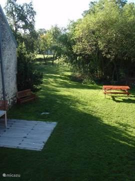 Het zicht op de tuin vanuit de slaapkamer. De eerste zon van de dag valt op de picknickbank. Aan het einde van de dag staat de bank weer in de zon. Maar overdag staat hij in de schaduw van de vlierbesboom.
