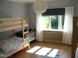 Een grote slaapkamer op de 1e verdieping met 2 stapelbedden