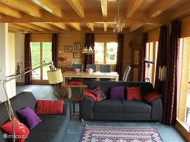 Een ruime woonkamer met zithoek rond de haard en een eettafel bij de open keuken. Overal een prachtig, vrij uitzicht op de bergen.