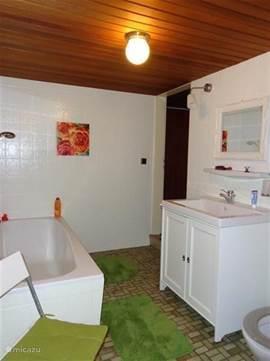 De ruime badkamer met heerlijk ligbad en separate douche Ruim badmeubel met genoeg bergruimte, wastafel en spiegel, voor de dames ligt er een fohn ..