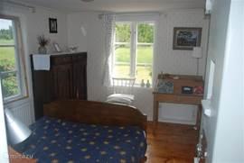 Ouderslaapkamer met uitzicht op de voortuin.