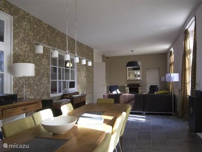 De grote woonkamer met open haard heeft een leuke zithoek met loungebank en een eethoek met ruimte voor 8 personen.