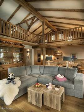 The living room with loft and sloping beamed ceiling has a warm atmosphere and is decorated in typical Austrian style
