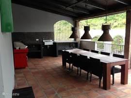 Het grote terras met  buitenkeuken en een boretti barbecue.