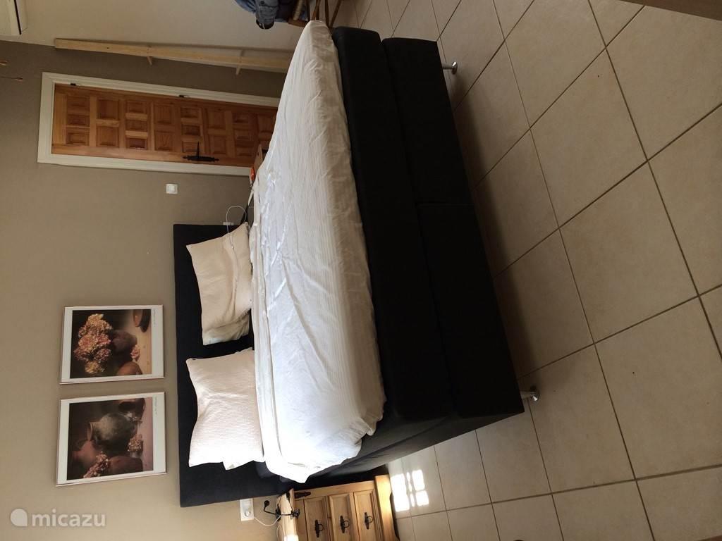 De grootste slaapkamer met een king-sizebed, voldoende kastruimte en doorgang naar de badkamer.