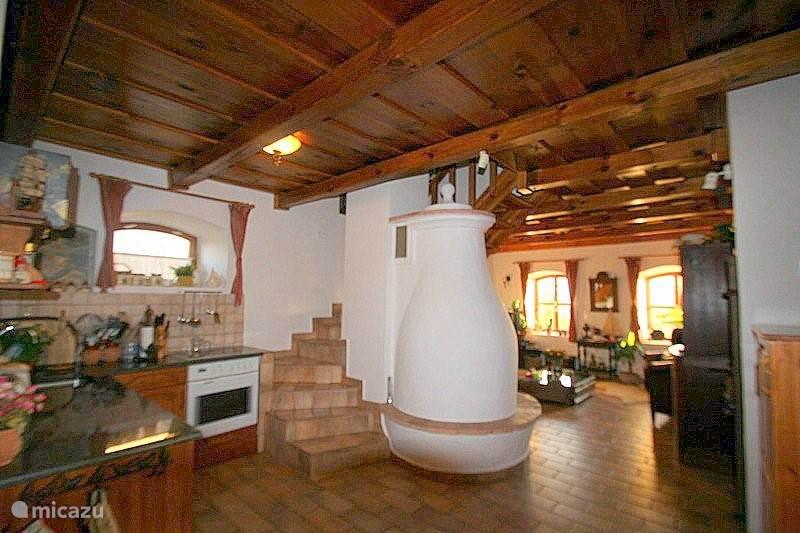 Blik vanuit eethoek op keuken,, opgang naar de bovenverdieping en de woonkamer