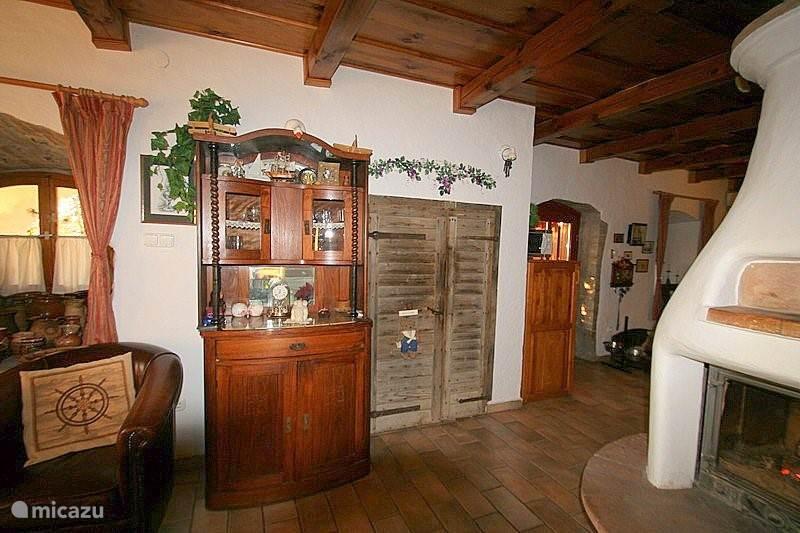 Woonkamer zicht op 200 jaar oude wijndeur, waar tevens de ingang van binnen naar de wijnkelder is. Dit is zeer bijzonder middels die oude deur, daar het bijna niet voorkomt om vanuit binnen in een wijnkelder te komen.
