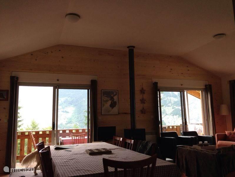 Riante woonkamer voor 10 personen met in het midden de houtkachel