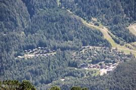 Chalet ligt aan de linkerkant van het dorp. Aan de bovenkant ziet u de piste die bij de liften uitkomt.
