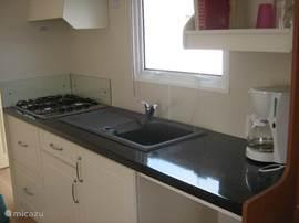 Open keuken met o.a. koel/vriescombi koffiezetter, afzuigkap en 4 pits gasstel