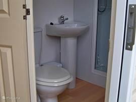 Badkamer met douchecabine, wastafel en toilet