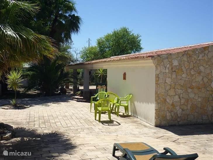Nogmaals: het zonneterras voor het huis tussen de palmen. Op de achtergrond het grote overdekte terras (6 bij 15m)