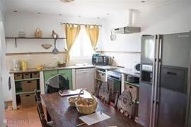 De keuken met grote koelkast, eettafel, aanrecht, etc.