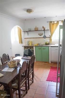 De keuken met achterin de ingang naar de bijkeuken waar voorraden, keukenvoorraden en de wasmachine staan