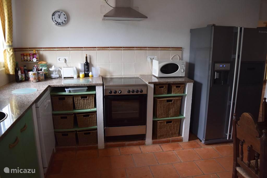 Keuken met alle apparatuur. Grote koelkast met vriezer, vaatwasser, magnetron, kookpitten en luxe oven.
