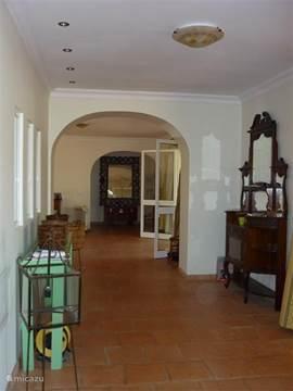 Hal met entree rechts en doorkijk naar woonkamer met openslaande deuren naar overdekt terras