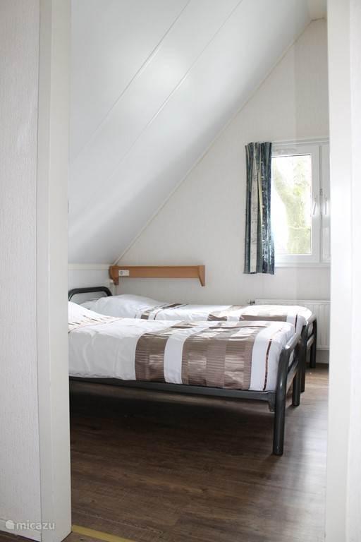 De slaapkamer met drie bedden en nieuwe matrassen
