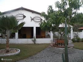 front of the house with large veranda and beautiful garden with fruit trees, palms and bougainvilleas