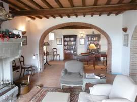 woonkamer met openhaard en zicht op bibliotheek