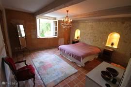 Ouderslaapkamer met een comfortabel tweepersoonsbed, een dressing en doorloop naar de badkamer.