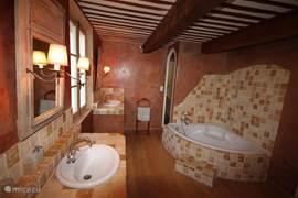 De badkamer met hoekbad, twee wastafels en een massagedouche