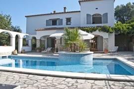 Aanzicht van de achterzijde van villa SOLVINA met zicht op zwembad en terrassen.