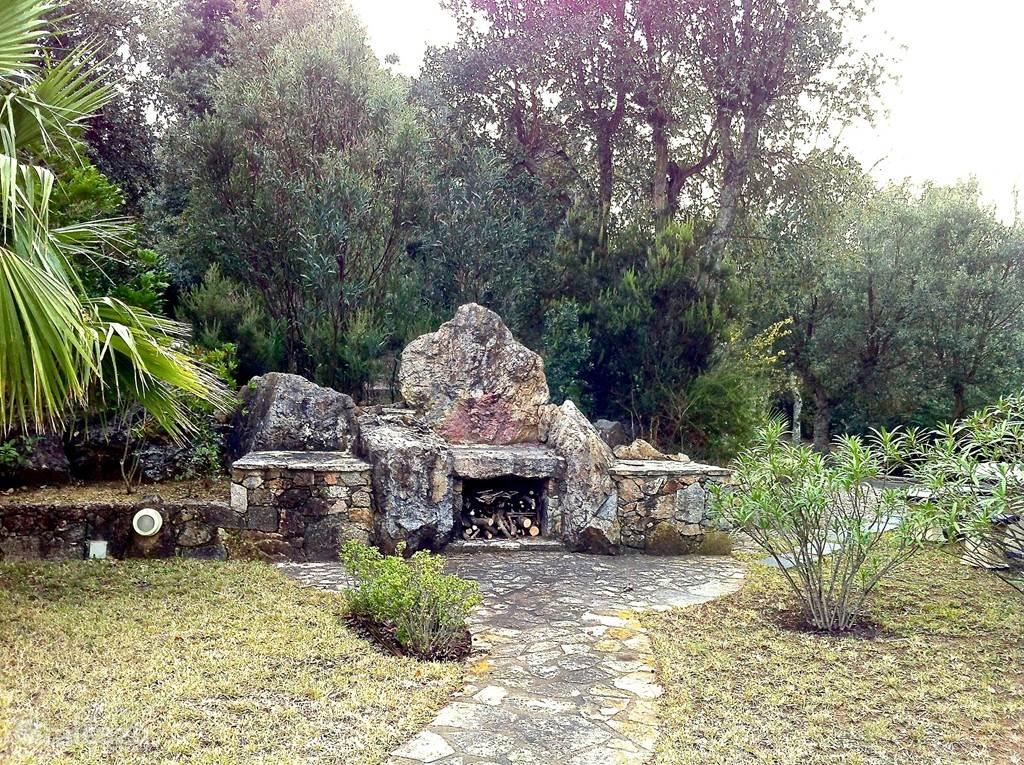 Barbecueplaats met rechts een stenen tafel met banken