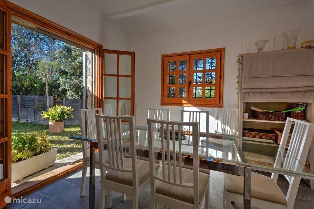 De eetkamer met openslaande deuren naar de achtertuin met zwembad.