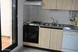 Kitchen with dishwasher and oven, on the right is also a fridge-freezer and a microwave.