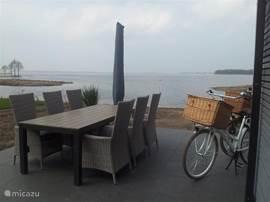 Esstisch mit 6 Stühlen sowie Sonnenschutzmittel. Mit direktem Blick auf das Veluwemeer.