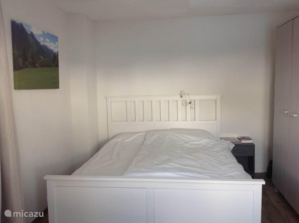 De slaapkamer met tweepersoons bed, kast en kaptafel en fenomenaal uitzicht op de bergen/