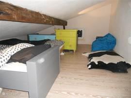 De slaapzolder met drie losse bedden welke bereikbaar is met de trap vanuit de woonkamer. Stahoogte alleen in de nok.