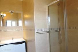 De badkamer met wastafel en ruime douche. Het toilet is apart van de badkamer.