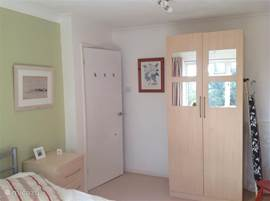 The master bedroom, the bed is free with nightstands on either side and a spacious wardrobe.